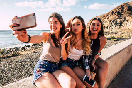 Millennial girls taking selfie picture with modern phone for social media having lot of fun together in friendship - smile and crazy expression people outdoor at the beach for summer holiday Stockfoto