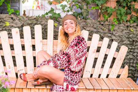 Portrait of cheerful pretty blonde young woman sitting on a handmade pallets wooden bench and looking at the camera outdoor Stockfoto