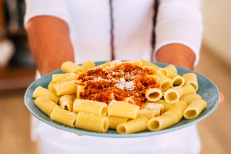 Close up of fresh and tasty italian pasta food with bolognese ragu sauce - unrecognizable man defocused in background like chef or worker in restaurant