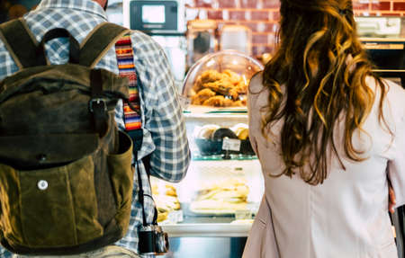Couple of people looking and choosing food inside a bakery bar shop - concept of travel and business nutrition Stockfoto