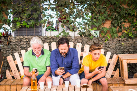 family generations men with grandfather father and son nephew from old to young stay together using cellular technology smartphone to connect to internet and check modern related concepts. caucasian people Stockfoto