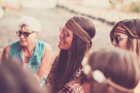 Hippy vintage concept with group of ladies together in friendship - brown colors filter and sun flowers period - alternative people in different love lifestyle Stockfoto