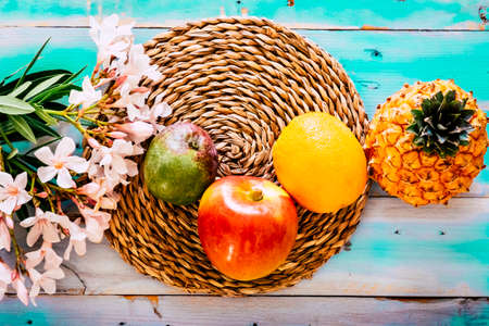 Above colored food view with vitamins fresh seasonal fruits on a blue yellow table with flowers decoration