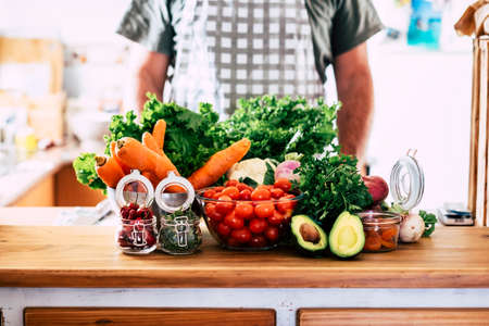 Variety of fruits and vegetables at home or kitchen restaurant with unrecognizable chef in background - concept of diet and vegetarian or vegan food nutrition healthy lifestyle - natural seasonal vitamin table ingredients Stockfoto