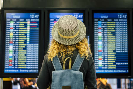 Travel people in airport or train station concept - view from rear of a blonde curly female woman with blue backpack looking and checking time departures or arrivals on the displays screen