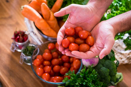 Close up of hands holding fresh and red colored cherry tomatoes and various mix vegetables in backgraound cof healthy food nutrition concept lifestyle