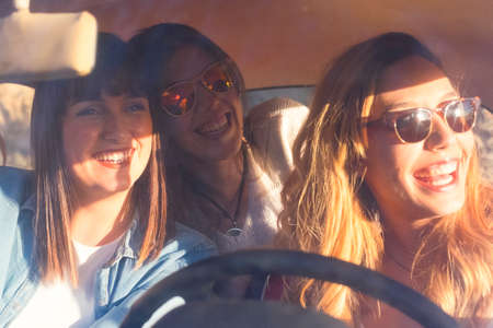 Group of cheerful happy and beautiful sunny friends young woman inside a car enjoy and have fun together traveling and driving - concept of youthful and joy people