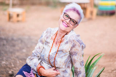 Beautiful alternative senior mature woman with punk hipster hippy style white and violet hair smile at the camera posing for a portrait - happiness and retired lifestyle concept Stockfoto