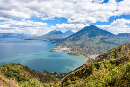 Viewpoint at lake Atitlan with the three volcanos San Pedro, Atitlan and Toliman - you can see the small villages San Pedro and San Juan at the lake in the highlands of Guatemala Stock Photo