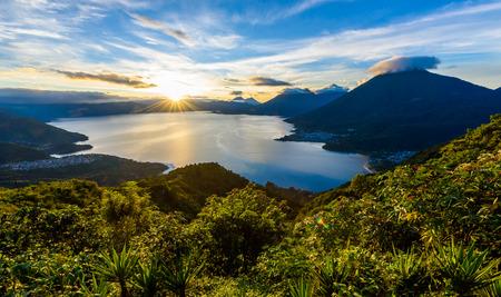 Sunrise in the morning at lake Atitlan, Guatemala - amazing panorama view to the volcanos San Pedro, Toliman and Atitlan 스톡 콘텐츠
