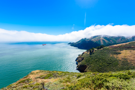 Coast at Golden Gate Bridge in clouds on a beautiful summer day  - Panoramic view from Battery Spencer - San Fancisco Bay Area,  Golden Gate National Recreation Area, California, USA