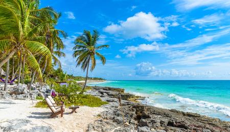 Stühle unter den Palmen auf Paradiesstrand am tropischen Resort . Riviera Maya - Karibikküste in Tulum in Quintana Roo Standard-Bild - 91169648