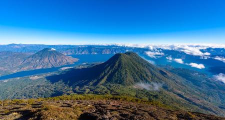 Panorama view of Lake Atitlan and volcano San Pedro and Toliman early in the morning from peak of volcano Atitlan, Guatemala. Hike on Vulcano Atitlan.