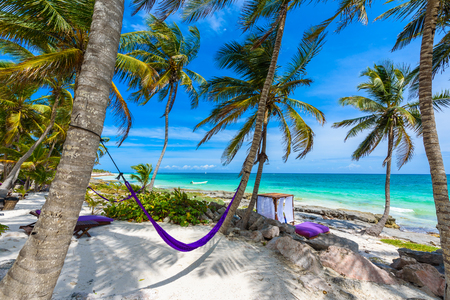 Beach beds and Hammock under the palm trees on paradise beach at tropical Resort. Riviera Maya - Caribbean coast at Tulum in Quintana Roo, Mexico Stock Photo