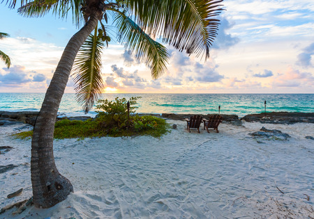 Sunset at paradise beach - Chairs under the palm trees on beach at tropical Resort. Riviera Maya - Caribbean coast at Tulum in Quintana Roo, Mexico Stock Photo