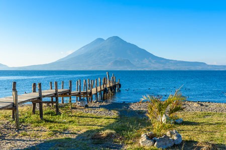 Wooden pier at Lake Atitlan on the beach in Panajachel, Guatemala.  With beautiful landscape scenery of volcanoes Toliman, Atitlan and San Pedro in the background. Фото со стока
