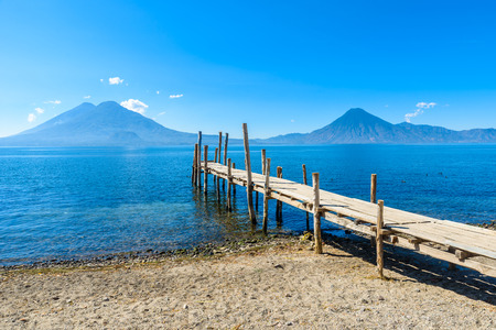 Wooden pier at Lake Atitlan on the beach in Panajachel, Guatemala.  With beautiful landscape scenery of volcanoes Toliman, Atitlan and San Pedro in the background. Stock Photo