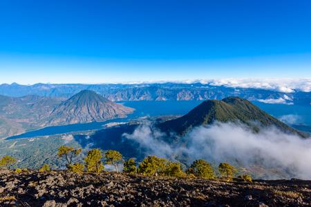 Panorama view of Lake Atitlan and volcano San Pedro and Toliman early in the morning from peak of volcano Atitlan, Guatemala. Hike on Vulcano Atitlan. Stock Photo - 91170121