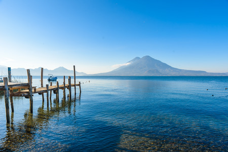 Wooden pier at Lake Atitlan on the beach in Panajachel, Guatemala. With beautiful landscape scenery of volcanoes Toliman, Atitlan and San Pedro in the background. Volcano Highland in Central America. Stock Photo