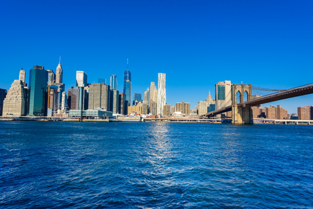 Brooklyn Bridge and the Lower Manhattan skyline panorama from Brooklyn Bridge Park riverbank, New York City, USA