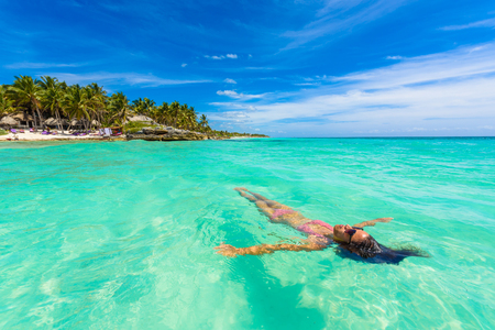 Attractive young woman relaxing in turquoise waters of Caribbean Sea in front of paradise beach in Tulum, close to Cancun, Riviera Maya, Mexico