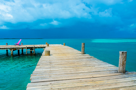 Tobacco Caye - Relaxing on Wooden Pier on small tropical island at Barrier Reef with paradise beach, Caribbean Sea, Belize, Central America