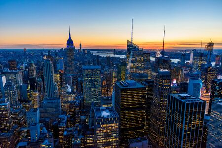 New York City skyline at night - skyscrapers of midtown Manhattan with Empire State Building at Amazing Sunset - USA Stock Photo