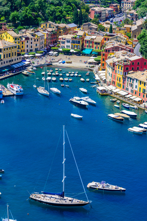 Portofino, Italy - colorful houses and yacht in little bay harbor. Liguria, Genoa province, Italy. Italian fishing village with beautiful sea coast landscape in summer season. Stock Photo