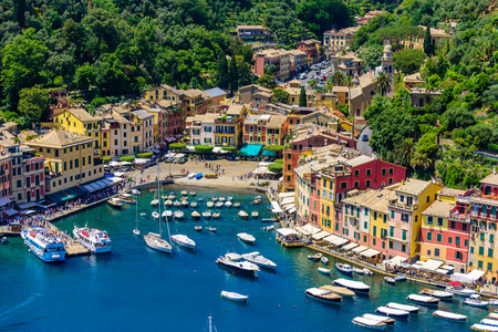 Portofino, Italy - colorful houses and yacht in little bay harbor. Liguria, Genoa province, Italy. Italian fishing village with beautiful sea coast landscape in summer season. 免版税图像