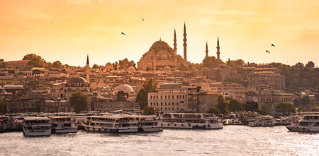 Eminonu Port with Ships and Suleymaniye Mosque in the Fatih district at Golden Horn River before sunset, Istanbul, Turkey. Travel concept and Sea front landscape of Istanbul historical part. Stock fotó