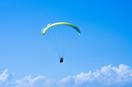 Paraglider is flying in the blue sky against the background of clouds. Paragliding in the sky on a sunny day. Extrem Sport and recreation. Foto de archivo - 111286248
