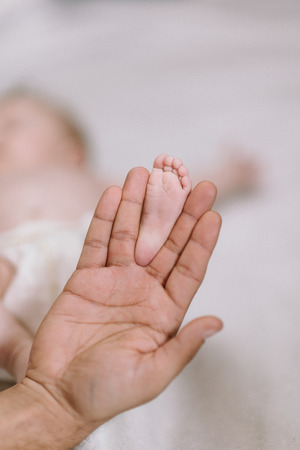 Baby feet in the hands of mother - cute newborn in the hands of mum - happy family moments