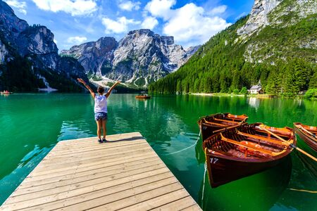 Woman relaxing on Pier at Lake Braies also known as Pragser Wildsee  in beautiful mountain scenery. Amazing Travel destination Lago di Braies in Dolomites, South Tyrol, Italy, Europe.