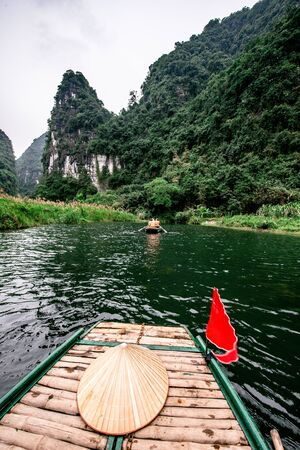 Boat cave tour in Trang An Scenic Landscape formed by karst towers and plants along the river. Its Halong Bay on land of Vietnam. Ninh Binh province, Vietnam.