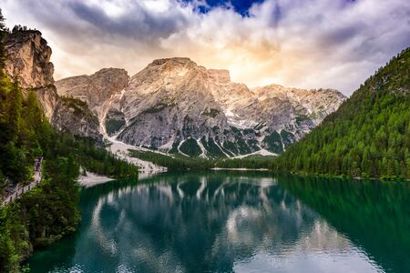 Lake Braies also known as Pragser Wildsee  in beautiful mountain landscape. Sun and cloud scenery at sunset time. Amazing Travel destination Lago di Braies in Dolomites, South Tyrol, Italy, Europe.