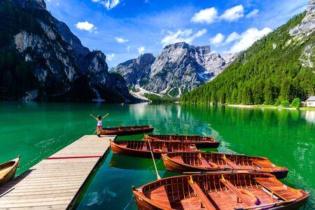 Frau entspannt am Pier am Pragser Wildsee auch bekannt als Pragser Wildsee in schöner Berglandschaft. Erstaunliches Reiseziel Lago di Braies in Dolomiten, Südtirol, Italien, Europa. Standard-Bild