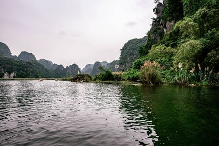 Boat cave tour in Trang An Scenic Landscape formed by karst towers and plants along the river. It's Halong Bay on land of Vietnam. Ninh Binh province, Vietnam. Reklamní fotografie