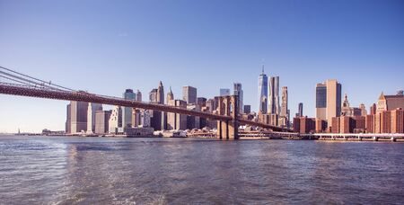 Famous Skyline of downtown New York City, Brooklin Bridge and Manhattan with skyscrapers illuminated over East River panorama. New York, USA