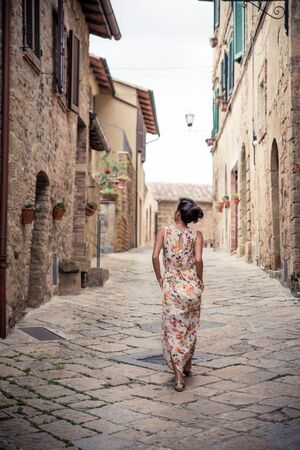 Young asian girl walking in Monticchiello town on summer day. Amazing promenade with traditional old stone houses - Tuscany, Italy, Europe 免版税图像