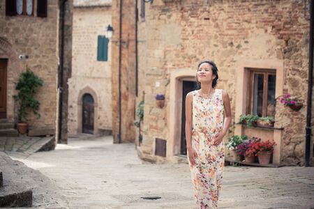 Young asian girl walking in Monticchiello town on summer day. Amazing promenade with traditional old stone houses - Tuscany, Italy, Europe Banco de Imagens