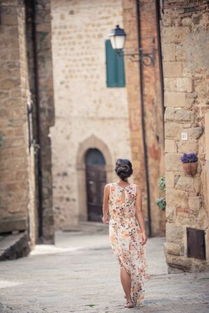 Young asian girl walking in Monticchiello town on summer day. Amazing promenade with traditional old stone houses - Tuscany, Italy, Europe Stok Fotoğraf