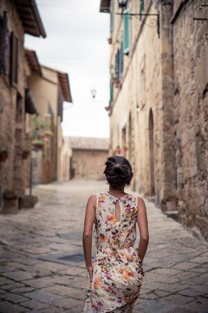 Young asian girl walking in Monticchiello town on summer day. Amazing promenade with traditional old stone houses - Tuscany, Italy, Europe Stockfoto