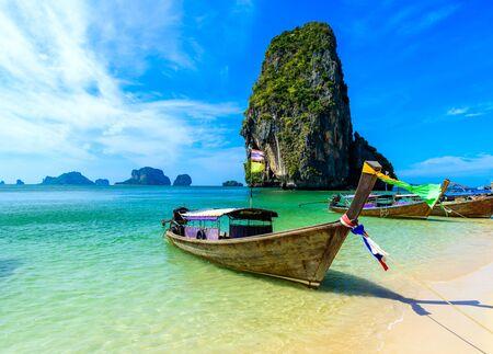 Ao Phra Nang Beach - tajska tradycyjna drewniana łódź typu longtail na półwyspie Railay przed wapiennymi skałami krasowymi, w pobliżu Ao Nang, prowincja Krabi, Morze Andamańskie, Tajlandia Zdjęcie Seryjne