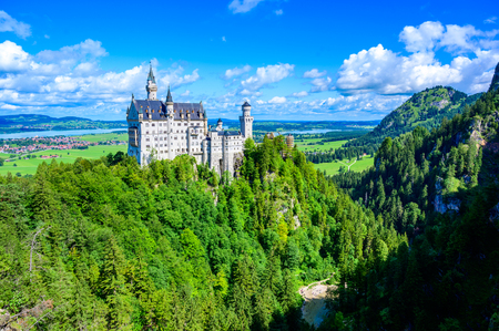 Neuschwanstein Castle in beautiful mountain scenery of Alps- in the background you can see the Lake Forggensee - near Fuessen, Bavaria, Germany 新闻类图片