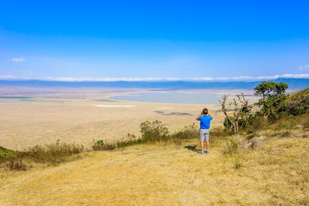 Tourist looks into the Ngorongoro crater National Park with the Lake Magadi. Safari Tours in Savannah of Africa. Beautiful landscape scenery in Tanzania, Africa Banque d'images