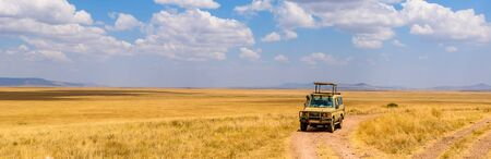 Safari tourists on game drive with car in Serengeti National Park in beautiful landscape scenery, Tanzania, Africa