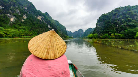 Tam Coc Natioanl Park - Vietnamese Girl traveling in boat along the Ngo Dong River at Ninh Binh Province, Trang An landscape complex, Landscape formed by karst towers and rice fields - Vietnam