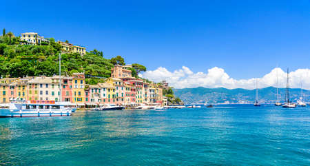 Portofino, Italy - Harbor town with colorful houses and yacht in little bay. Liguria, Genoa province, Italy. Italian fishing village with beautiful sea coast landscape in summer season.