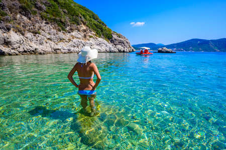 Girl with sun hat relaxing and swimming at Porto Timoni beach at Afionas is a paradise double beach with crystal clear azure water in Corfu, Ionian island, Greece, Europe Standard-Bild