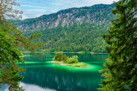 Small islands  pine trees in  middle of Eibsee lake  Zugspitze mountain. Beautiful landscape scenery  paradise beach and clear  water in German Alps, , Germany, Europe.